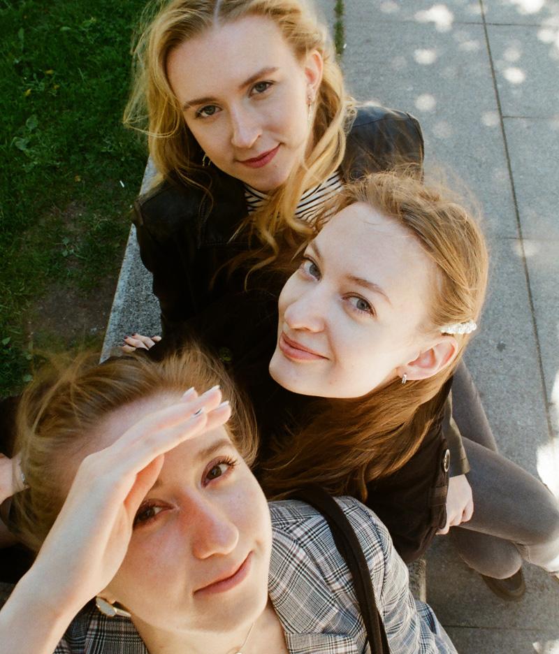 Drei junge Frauen schauen in Kamera